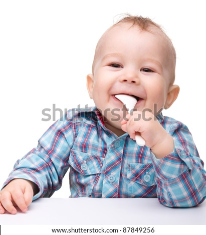 Cute little boy is biting spoon while sitting at table, isolated over white - stock photo