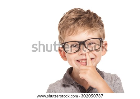 Cute little boy is isolated on white background. Boy wearing glasses, looking at camera, cheerfully smiling and picking his nose - stock photo