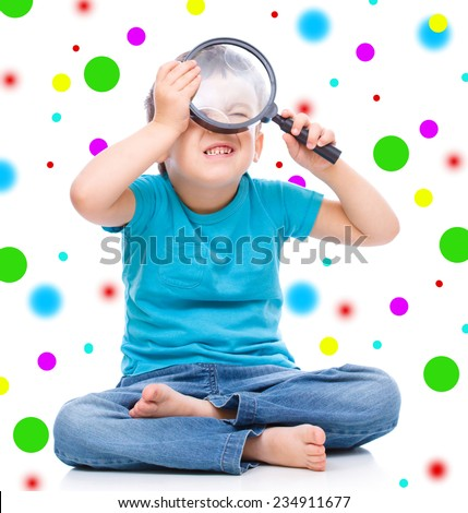 Cute little boy is looking through magnifier, isolated over background - stock photo