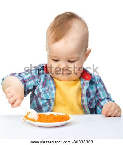 Cute little boy is playing with carrot salad, isolated over white - stock photo