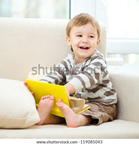 Cute little boy is reading book while sitting on a sofa - stock photo