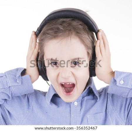 Cute little boy is screaming and listening to music - stock photo
