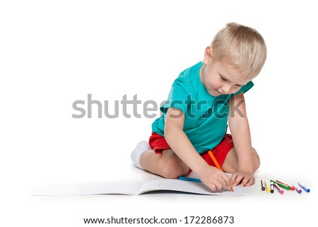 Cute little boy is sitting on the floor and drawing on paper - stock photo
