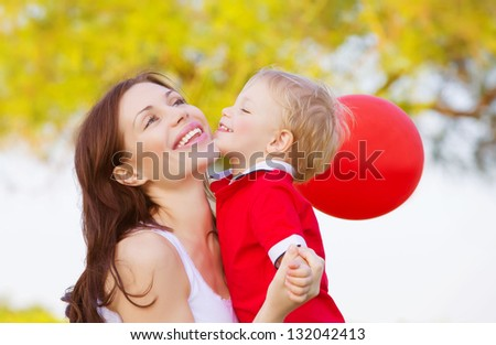 Cute little boy kissing mom, beautiful brunette woman with adorable child having fun outdoor in spring time, small kid with red balloon enjoying nature, happy family - stock photo
