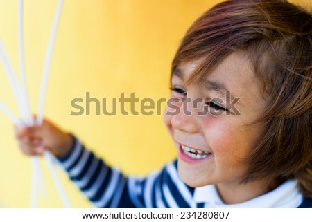 cute little boy laughing and smiling on a yellow background - stock photo