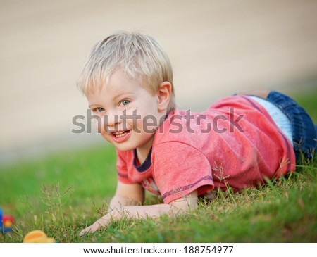 Cute lIttle boy lies on the grass outdoors and smiles at the camera - stock photo