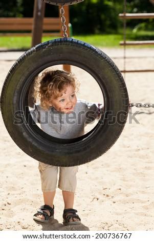 Cute little boy looking through tire swing - stock photo