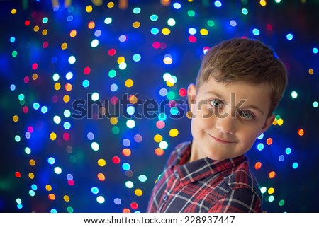 cute, little boy on  Christmas lights background - stock photo