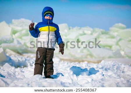 Cute little boy outdoors standing on winter beach on beautiful winter day - stock photo