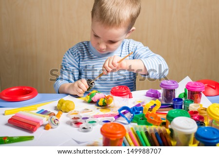 Cute little boy painting at the table - stock photo