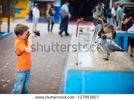 Cute little boy photographing at seafood market - stock photo