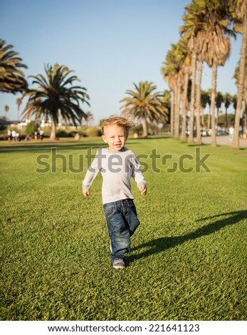 Cute little boy playing at a grassy park - stock photo