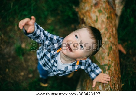 cute little boy playing in the green forest - stock photo