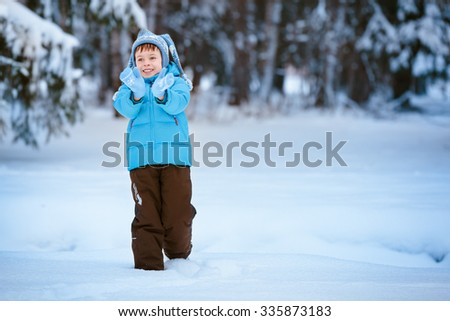 Cute little boy playing outdoors on winter forest - stock photo