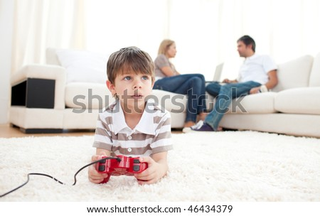 Cute little boy playing video games lying on the floor - stock photo