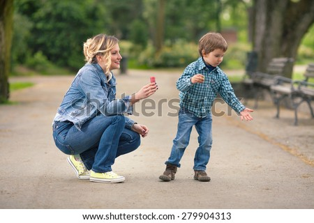 Cute little boy playing with his mother outdoors trying to catch soap bubbles - stock photo