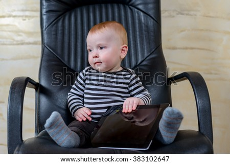 Cute Little Boy Playing with his Tablet Computer While Sitting on a Black Office Chair - stock photo