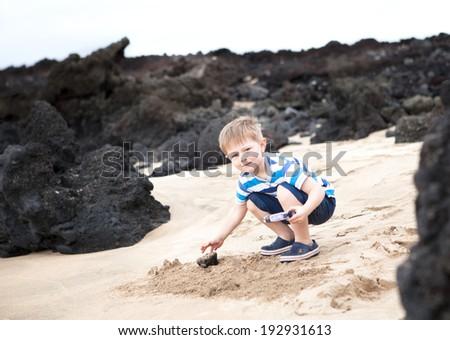 Cute little boy playing with lava rocks on a Maui beach - stock photo