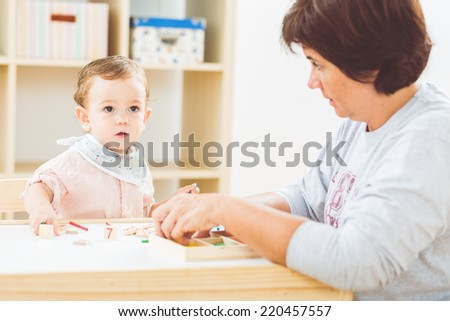 Cute little boy playing with numbers and sticks at the nursery school - stock photo