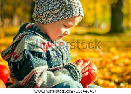 cute little boy playing with pumpkin in the park - stock photo