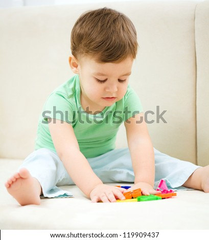 Cute little boy playing with toys while sitting on a couch, indoor shoot - stock photo