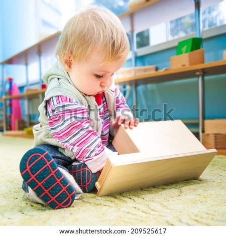 cute little boy plays with numerous bright toys - stock photo