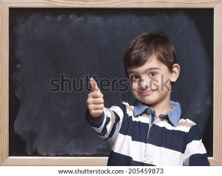Cute little boy posing in front of a blackboard - stock photo