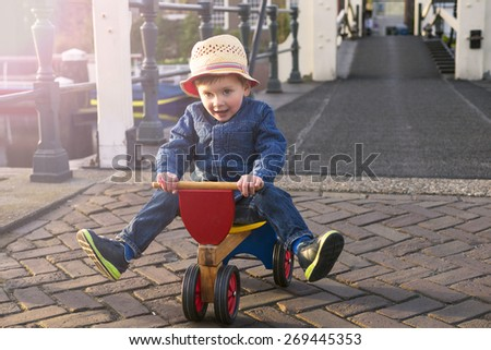 cute little boy riding his tricycle - stock photo