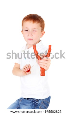 cute little boy shooting, focus on the slingshot - stock photo