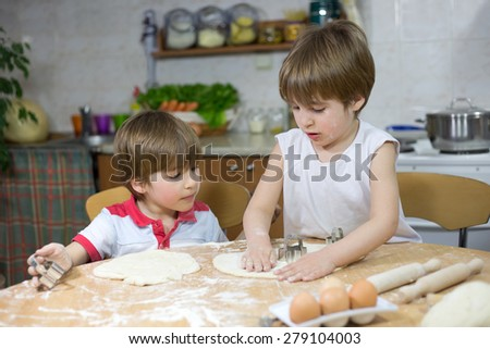 Cute Little Boy Showing His Twin Brother How to Flatten Dough at the Kitchen Table at Home - stock photo