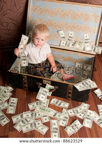 Cute little boy sitting in a suitcase with the money - stock photo