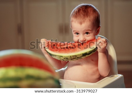 Cute little boy sitting in the child chair and biting big piece of watermelon. Image with toning and selective focus - stock photo