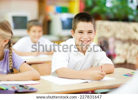 Cute little boy sitting in the classroom and smiling. Elementary age. Other kids in the background. - stock photo