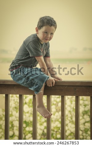 Cute little boy sitting on the backporch railing while enjoying his summer. Retro instagram look. - stock photo