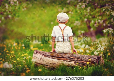 cute little boy sitting on wooden log, in spring garden - stock photo