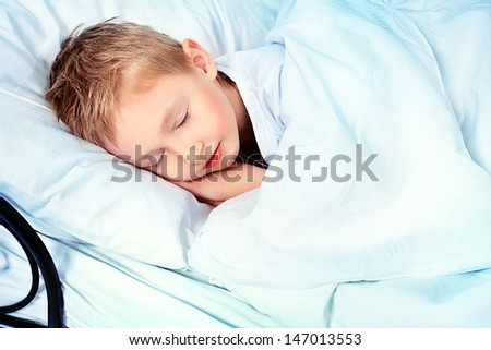 Cute little boy sleeping in a bed.  - stock photo