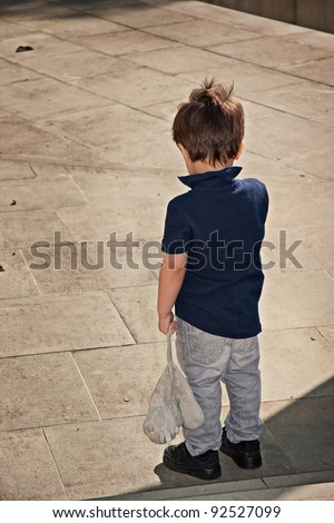 Cute little boy standing back and holding a stuffed toy - stock photo