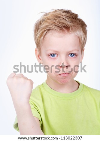Cute little boy threatening at camera with a fist - stock photo