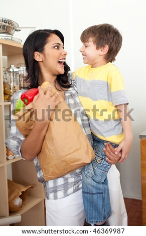 Cute Little boy unpacking grocery bag with his mother in the kitchen - stock photo