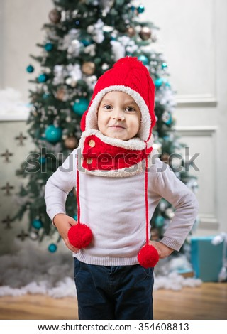 Cute little boy wearing winter hat and scarf while standing against Christmas tree at home - stock photo