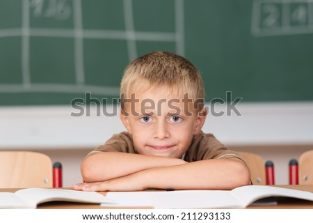 Cute little boy with a huge smile sitting at his desk in the classroom with his head resting on his hands looking at the camera - stock photo