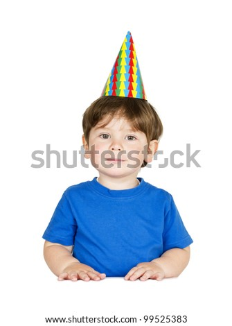 Cute little boy with a party hat at the table. Isolated on white. - stock photo