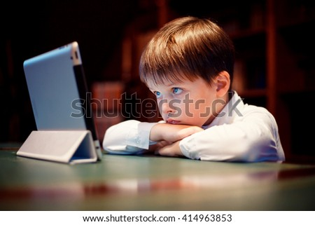 Cute little boy with a tablet pc indoors. Internet addiction and people concept  - stock photo
