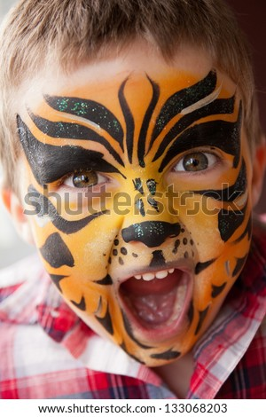 Cute little boy with a tiger make-up - stock photo