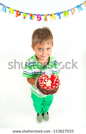 Cute little boy with birthday cake on birthday party. - stock photo