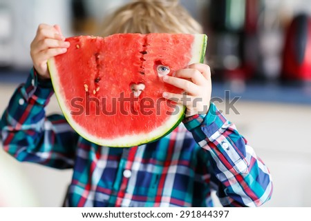 Cute little boy with blond hairs eating fresh watermelon. Healthy eating for kids - stock photo