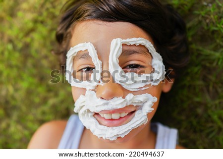 Cute little boy with cream making smiley face smiling - stock photo
