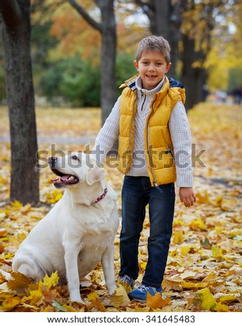 Cute little boy with his dog labrador retrievers outdoor in autumn beautiful park - stock photo