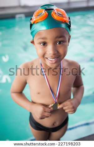 Cute little boy with his medal at the pool at the leisure center - stock photo