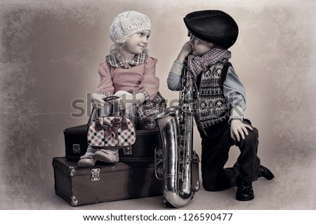 Cute little boy with his old saxophone is sitting on a suitcase with charming little lady. Retro style. - stock photo